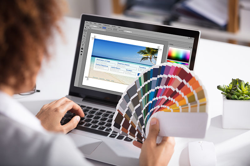 Close-up Of A Female Designer Holding Colorful Swatch Working On Laptop In Office