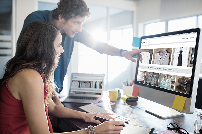 Man and woman in front of laptop designing an online shop