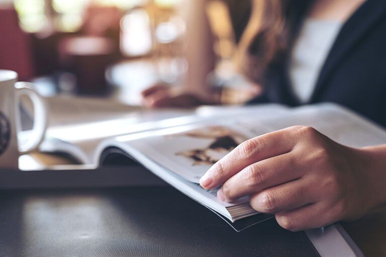 Closeup image of a businesswoman reading a book with coffee cup on table in cafe