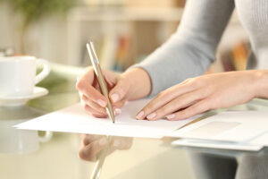 Close up of woman hands writing a letter sitting on a desk